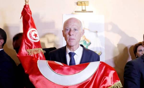 قيس سعيد يحمل العلم التونسي عقب إعلان فوزه بالانتخابات الرئاسية أمس الأول .(رويترز)