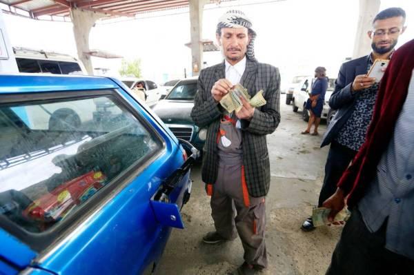 يمني يعد أمواله لدفع ثمن الوقود في محطة بنزين في صنعاء أمس الأول. (أ ف ب)