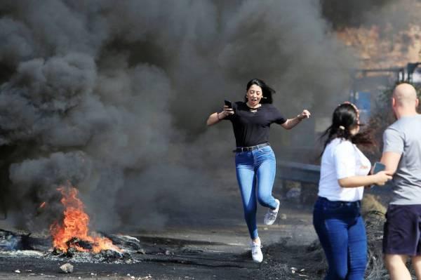 لبنانية تشق طريقها عبر إطارات محترقة تسد طريقا رئيسيا من جنوب لبنان إلى بيروت أمس. (رويترز)