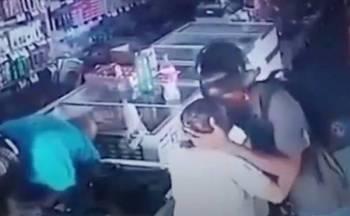 صورة من المقطع المتداول يظهر تقبيل اللص لرأس المسنة لتهدئتها.