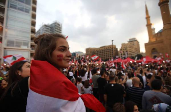 Lebanese demonstrators wave national flags as they take part in a rally in the capital Beirut's downtown district on October 20, 2019.  Thousands continued to rally despite calls for calm from politicians and dozens of arrests. The demonstrators are demanding a sweeping overhaul of Lebanon's political system, citing grievances ranging from austerity measures to poor infrastructure.  / AFP / Anwar AMRO