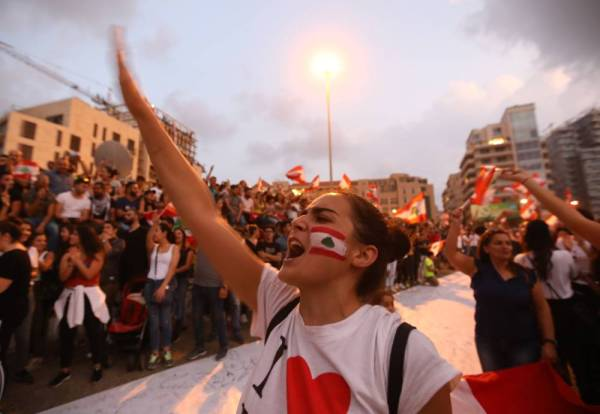Lebanese demonstrators chant slogans as they take part in a rally in the capital Beirut's downtown district on October 20, 2019.  Thousands continued to rally despite calls for calm from politicians and dozens of arrests. The demonstrators are demanding a sweeping overhaul of Lebanon's political system, citing grievances ranging from austerity measures to poor infrastructure.  / AFP / Anwar AMRO