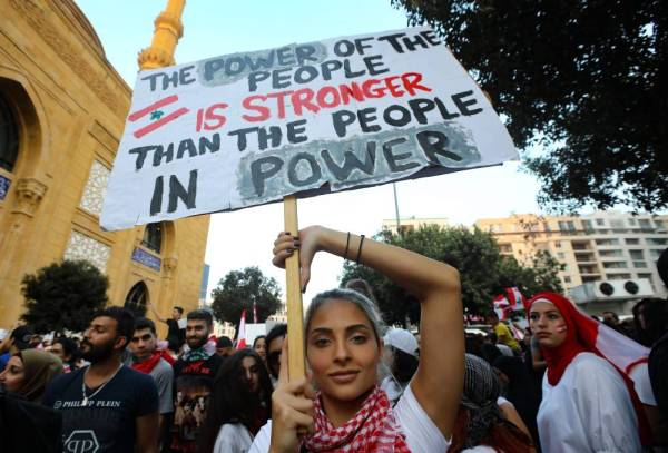 A Lebanese demonstrator carries a placard as she takes part in a rally in the capital Beirut's downtown district on October 20, 2019.  Thousands continued to rally despite calls for calm from politicians and dozens of arrests. The demonstrators are demanding a sweeping overhaul of Lebanon's political system, citing grievances ranging from austerity measures to poor infrastructure.  / AFP / Anwar AMRO