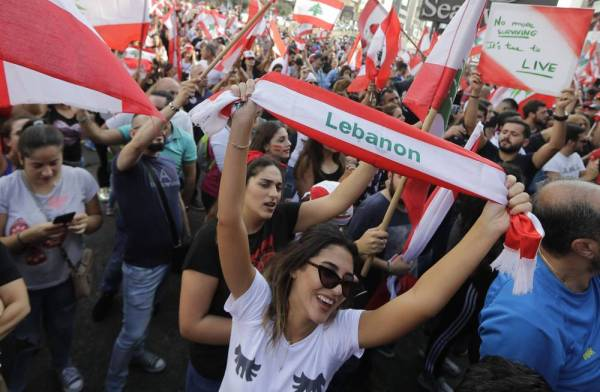 Lebanese demonstrators wave national flags on a highway linking Beirut to north Lebanon, in Zouk Mosbeh as they take part in a rally during the fourth day of demonstrations against tax increases and official corruption, on October 20, 2019. Thousands continued to rally despite calls for calm from politicians and dozens of arrests. The demonstrators are demanding a sweeping overhaul of Lebanon's political system, citing grievances ranging from austerity measures to poor infrastructure.  / AFP / Joseph EID
