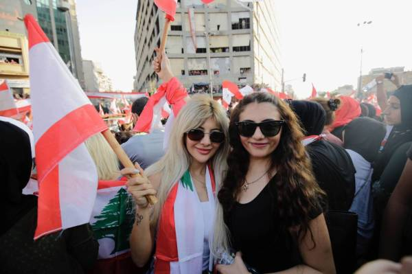 Lebanese protesters wave national flags as they take part in a rally in the northern city of Tripoli during the fourth day of demonstrations against tax increases and official corruption, on October 20, 2019. Thousands continued to rally despite calls for calm from politicians and dozens of arrests. The demonstrators are demanding a sweeping overhaul of Lebanon's political system, citing grievances ranging from austerity measures to poor infrastructure.  / AFP / Ibrahim CHALHOUB