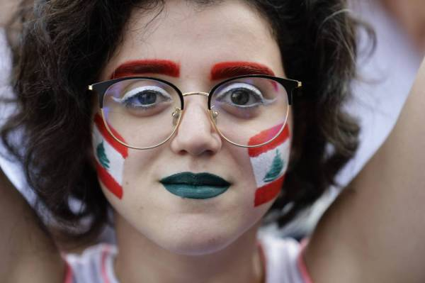 TOPSHOT - A Lebanese demonstrator with a national flag painted on her face takes part in a rally in Zouk Mosbeh, north of the capital Beirut, during the fourth day of demonstrations against tax increases and official corruption, on October 20, 2019. Thousands continued to rally despite calls for calm from politicians and dozens of arrests. The demonstrators are demanding a sweeping overhaul of Lebanon's political system, citing grievances ranging from austerity measures to poor infrastructure.  / AFP / Joseph EID
