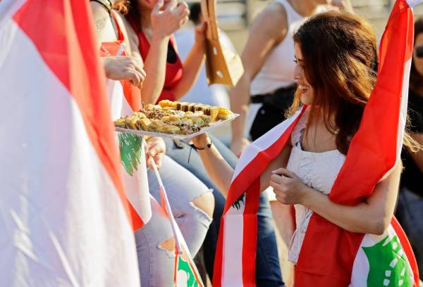 متظاهرة لبنانية تقدم الحلويات للمحتجين خلال الانتفاضة الشعبية شمالي بيروت