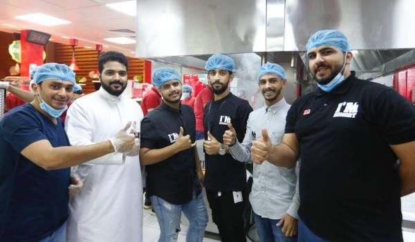 صورة جماعية لفريق العمل السعودي العاملين في المطعم.