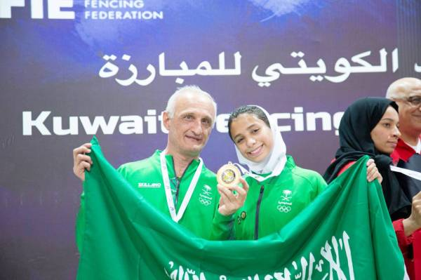 حسناء الحماد ترفع علم المملكة بعد الفوز بالميدالية الذهبية.
