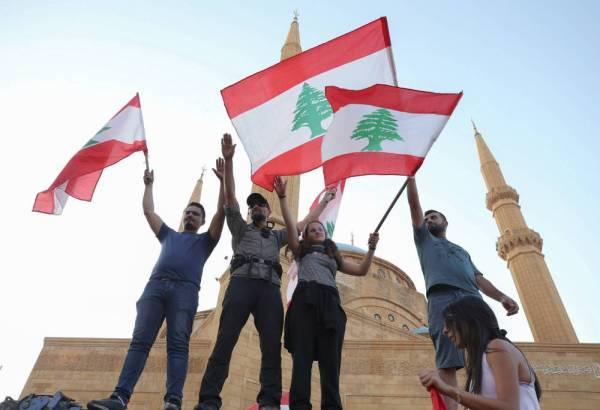 لبنانيون يحملون الأعلام الوطنية خلال مظاهرة مناهضة للحكومة في وسط بيروت أمس. (رويترز)