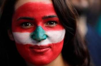 متظاهرة لبنانية لونت وجهها بعلم لبنان في مدينة صيدا الجنوبية، حيث تتواصل الاحتجاجات على الرغم من دعوات التهدئة من قبل الطبقة السياسية. (أ.ف.ب)