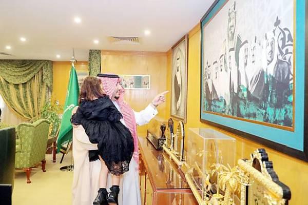 الأمير عبدالعزيز بن فهد بن تركي يطلع طفلة على لوحة تاريخية.