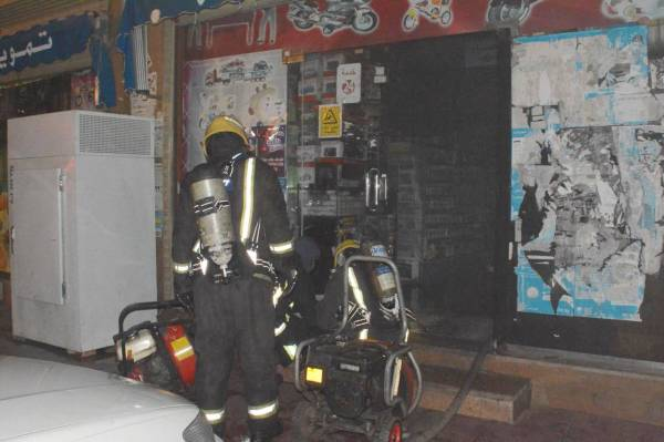 فرق الدفاع المدني خلال إخماد حريق محل تموينات محطة حي المروة.