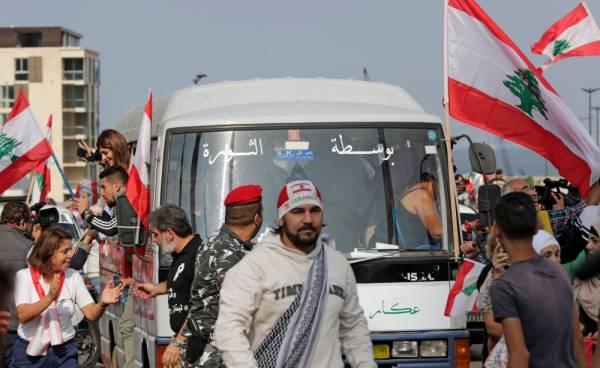 متظاهرون لبنانيون يرفعون العلم الوطني ويستقلون حافلة الثورة القادمة من شمال لبنان إلى الجنوب أمس. (أ ف ب)