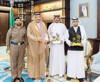 الأمير حسام بن سعود مع المكرمين. (عكاظ)