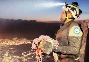 أحد أفراد الدفاع المدني السوري (الخوذ البيض) يحمل طفلة قتلت إثر غارة جوية روسية على بلدة معرة النعمان في محافظة إدلب. (أ.ف.ب)