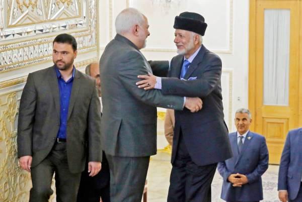 وزير خارجية الملالي جواد ظريف يستقبل نظيره العماني يوسف بن علوي في طهران أمس. (أ ف ب)