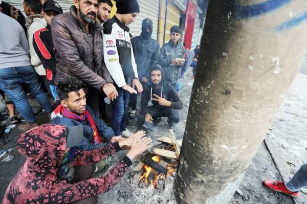 عراقيون يتجمعون في شارع الرشيد ببغداد خلال احتجاجات تطالب بإسقاط النظام أمس. (أ ف ب)