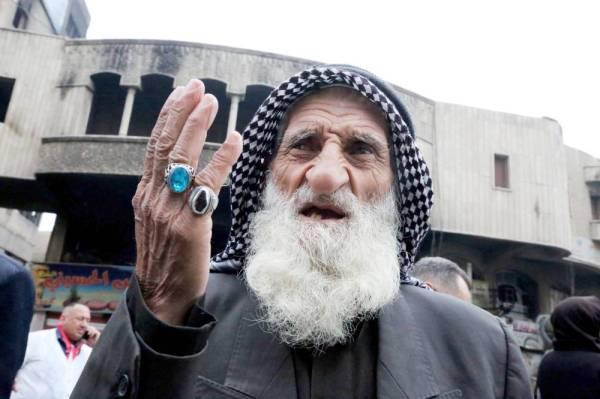 مسن عراقي يشارك في المظاهرات المستمرة ضد النظام في ميدان الخلاني في بغداد أمس. (أ ف ب)