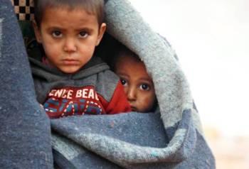 أطفال سوريون يحتمون ببطانية من البرد في مخيم للنازحين قرب تل عقرين في إدلب أمس الأول. (أ.ف.ب)