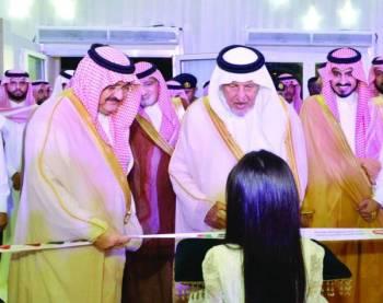 الأمير خالد الفيصل يداعب طفلة خلال افتتاح المعرض بحضور الأمير مشعل بن ماجد والأمير بدر بن سلطان.