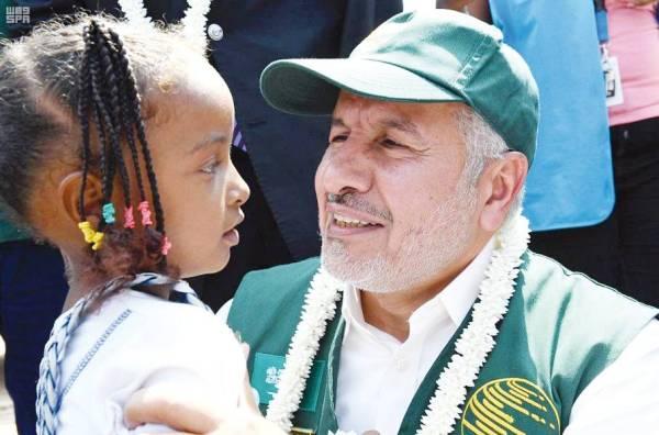 الربيعة مع طفلة أفريقية عند تسلمها معونة من مركز الملك سلمان للإغاثة.