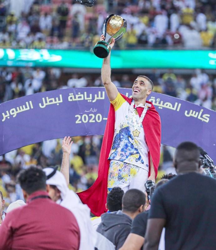المغربي حمدالله رافعا كأس السوبرالذي حققه مع فريقه النصر.