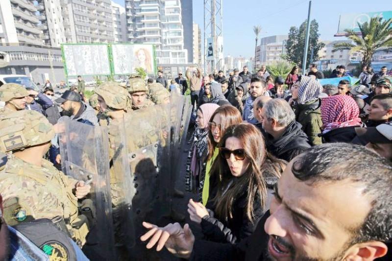 متظاهرون لبنانيون يقفون أمام حاجز أمني، في منطقة فرن الشباك قرب العاصمة بيروت، أمس.  (وكالات)