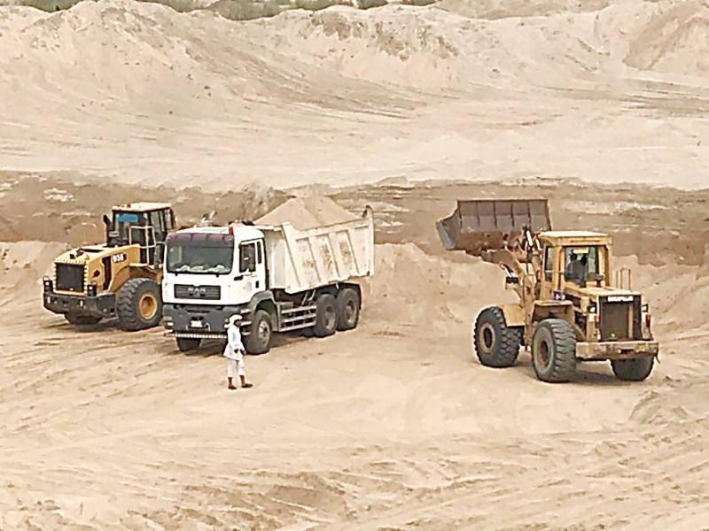 عربات النقل تنهل الرمال من وادي جازان. (عكاظ)