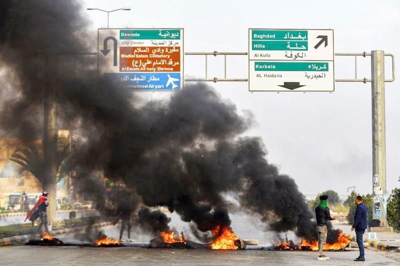 حرق إطارات وقطع طرق في النجف أمس، استعدادا ليوم غضب عارم في العراق. (وكالات)