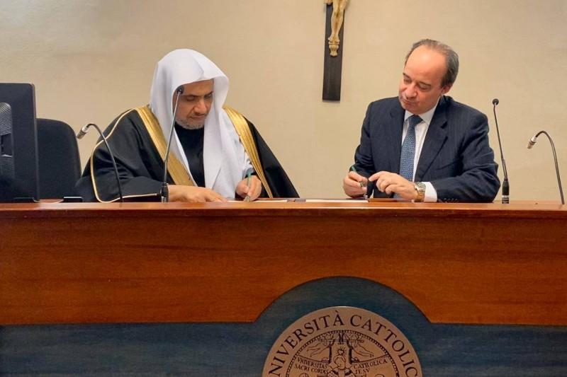 .العيسى ورئيس الجامعة الكاثوليكية أثناء توقيع الاتفاقية