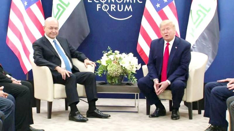 الرئيس العراقي برهم صالح أثناء لقائه الرئيس الأمريكي  على هامش منتدى دافوس الاقتصادي أمس. (وكالات)
