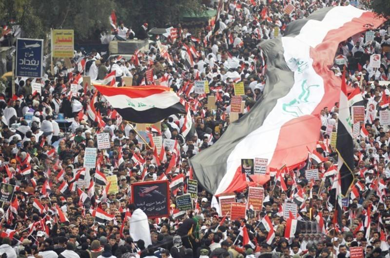 آلاف العراقيين يلوحون بأعلام وطنية خلال مظاهرة في وسط بغداد أمس، دعا إليها زعيم التيار الصدري مقتدى الصدر. (أ.ف.ب)