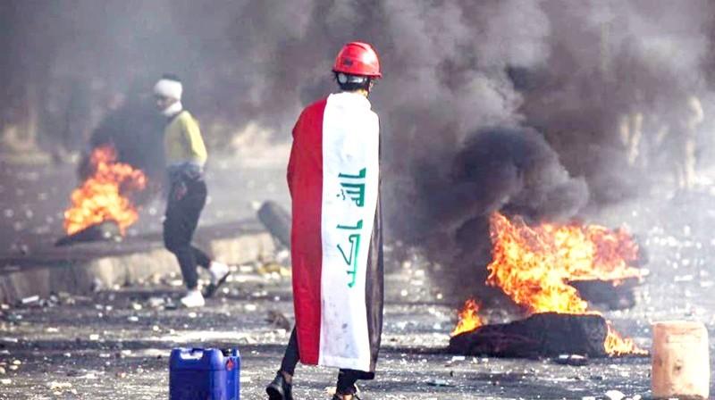متظاهر عراقي يقف أمام إطارات محترقة على أحد الجسور في بغداد أمس. (وكالات)