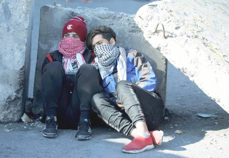 محتجان عراقيان يأخذان قسطاً من الراحة قرب أحد الجسور في وسط بغداد، أمس الأول (أ.ف.ب).