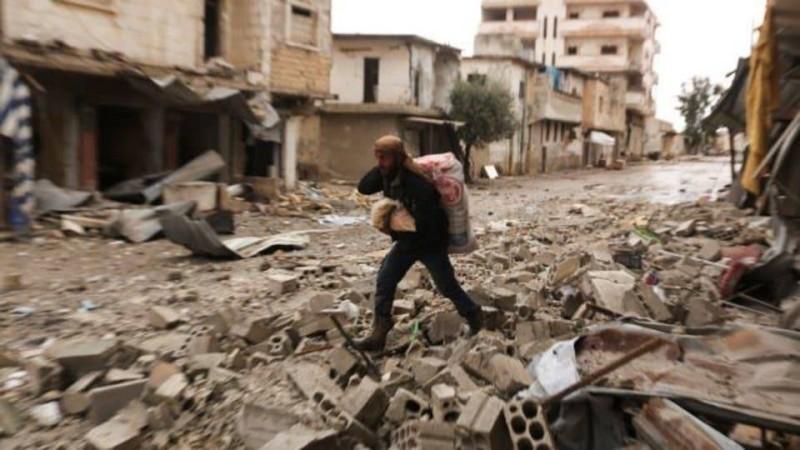 سوري يمر بين حطام المنازل حاملا معونات غذائية