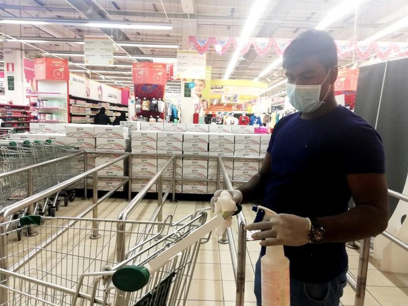 عامل في إحدى الأسواق يقوم بتعقيم وتطهير عربات التسوق.