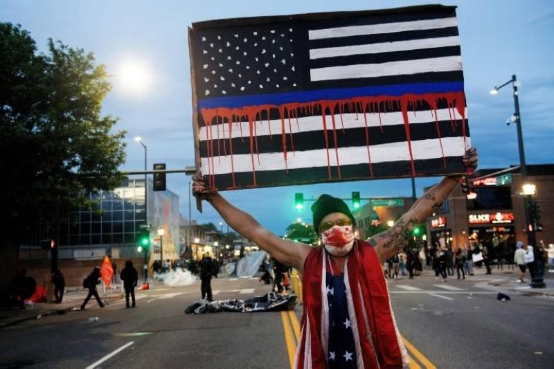 متظاهر يرفع لافتة خلال احتجاج في دنفر بولاية كولورادو (وكالات)
