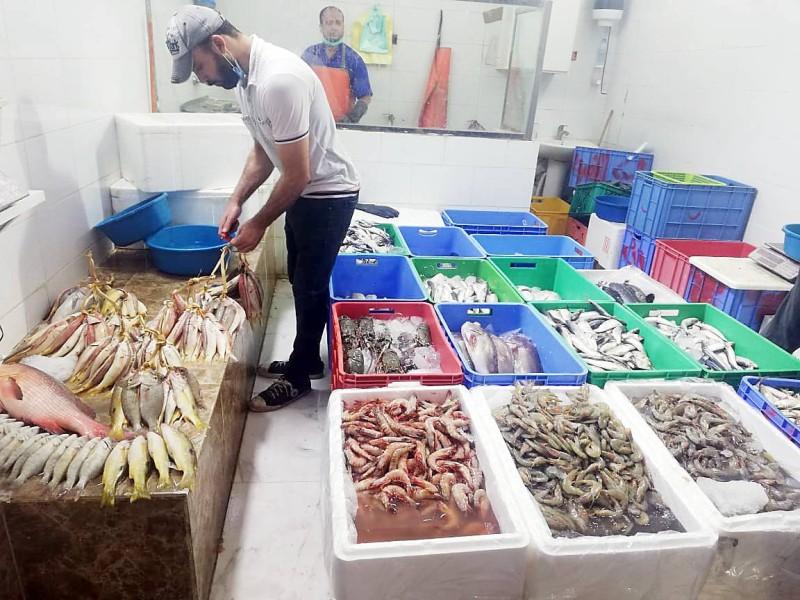 متعامل في أحد محلات الأسماك. (تصوير: حسام كريدي)