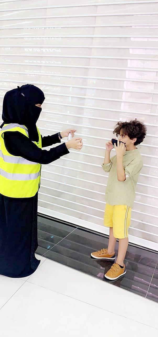 د. ابتهال تشرح لطفل كيفية ارتداء الكمامة. (عكاظ)
