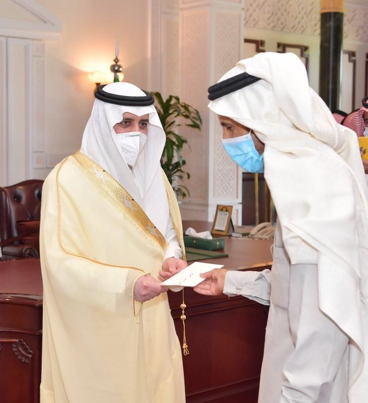 الأمير فهد بن سلطان خلال تسليمه التعويضات المالية أمس.  (عكاظ)