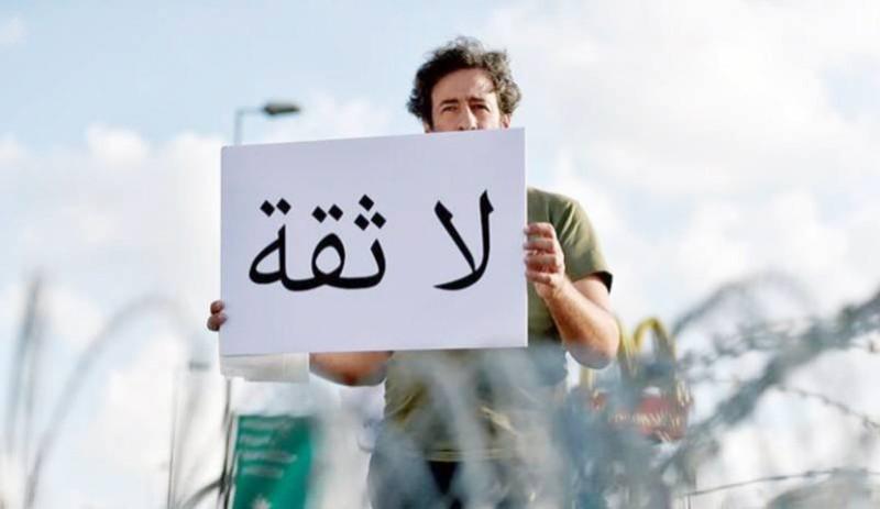 متظاهر لبناني يرفع لافتة، منددا بالوضع الاقتصادي والاجتماعي.