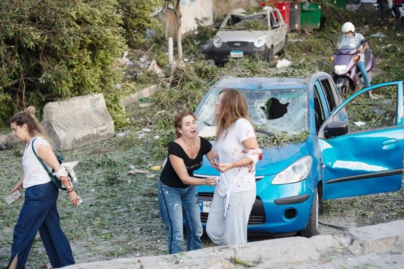 جريحات لبنانيات تبكين إثر التفجير المدمر الذي هز بيروت أمس، وفي الإطار آثار الدمار في الموقع.