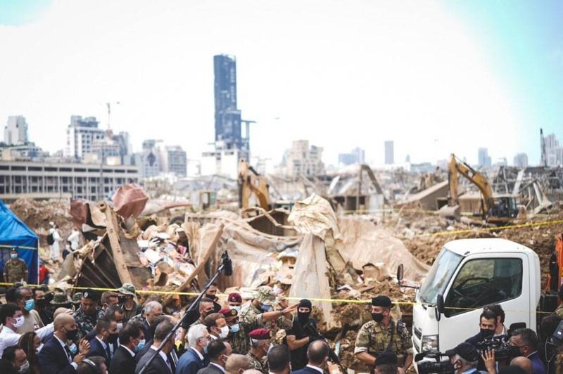 ماكرون متفقداً المنطقة المنكوبة في موقع انفجار مرفأ بيروت أمس، ومحاطاً بمسؤولين لبنانيين.  (الرئاسة الفرنسية)