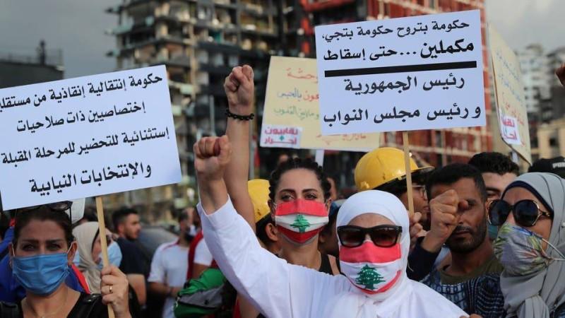 متظاهرون يرفعون لافتات تطالب بإسقاط رئيسي الدولة والبرلمان وتشكيل حكومة مستقلة.