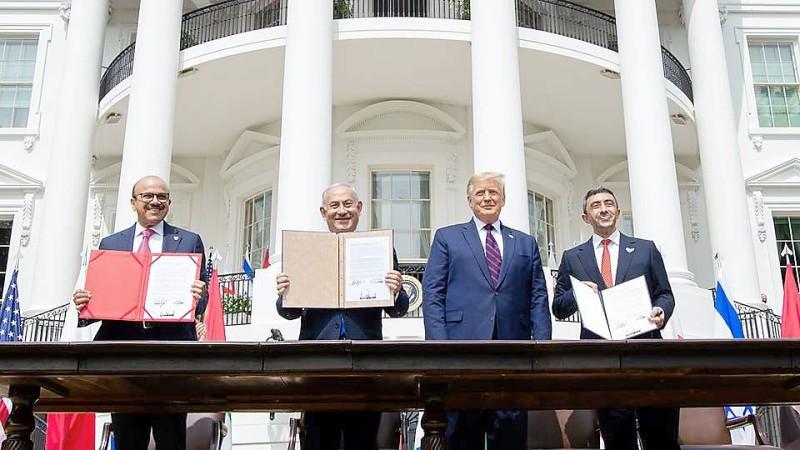 ترمب يتوسط نتنياهو وعبدالله بن زايد وعبداللطيف الزياني عقب التوقيع على اتفاقات السلام أمس.