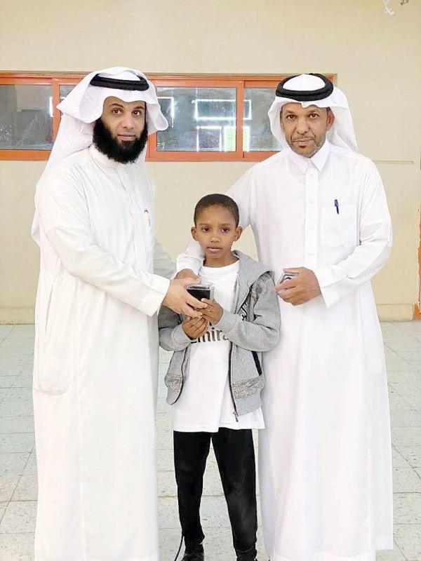 الرمثي مع أحد طلابه بحضور مدير المدرسة.