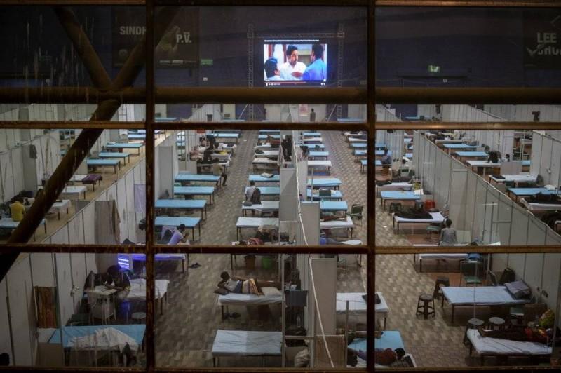 مصابون يشاهدون التلفزيون في مستشفى مؤقت في ملعب رياضي في نيودلهي.