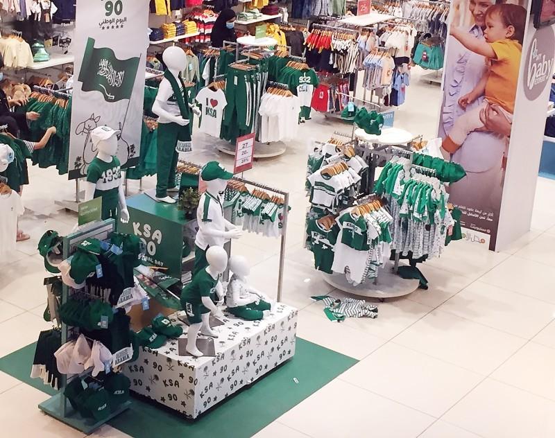 العديد من المحلات هيأت الملابس والشعارات الوطنية في الواجهة احتفالا باليوم الوطني.
