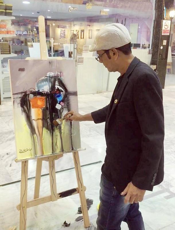 الفنان صادق غالب يرسم لوحته في الورشة.